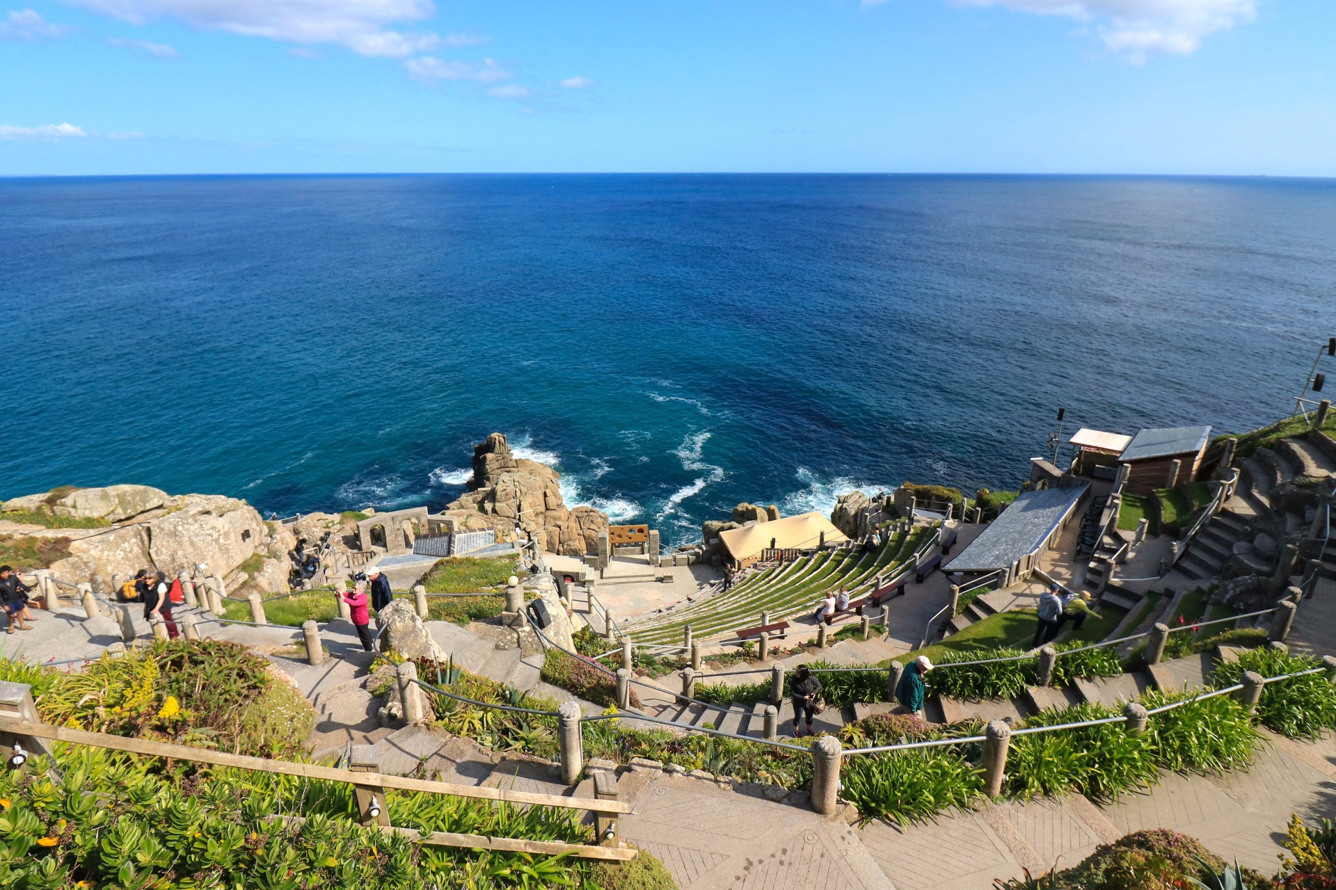 The Minack Theatre Porthcurno Beach Penzance Land's End. Summer. Blue skies. Historic Greek amphitheatre by blue, turquoise sea. 8 Great Day Trips from Exeter You Can't Miss. Exeter day trips. England, UK. Day trips from Devon. Day trips from Exeter Devon. Day trips from Exeter UK. Day trips from Exeter by train. Day tours from Exeter. Day tours from Exeter UK. Coach day trips from Exeter. Things to do in Exeter. Things to see in Exeter. Things to do in Devon. Exeter travel blog. Exeter travel guide. Bath. Bristol. Cardiff. Plymouth. English Riviera. Jurassic Coast. Dartmoor National Park. Cornwall. Click through to read more...