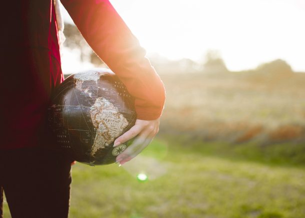 Women holding globe in hands girl earth outdoors green grass