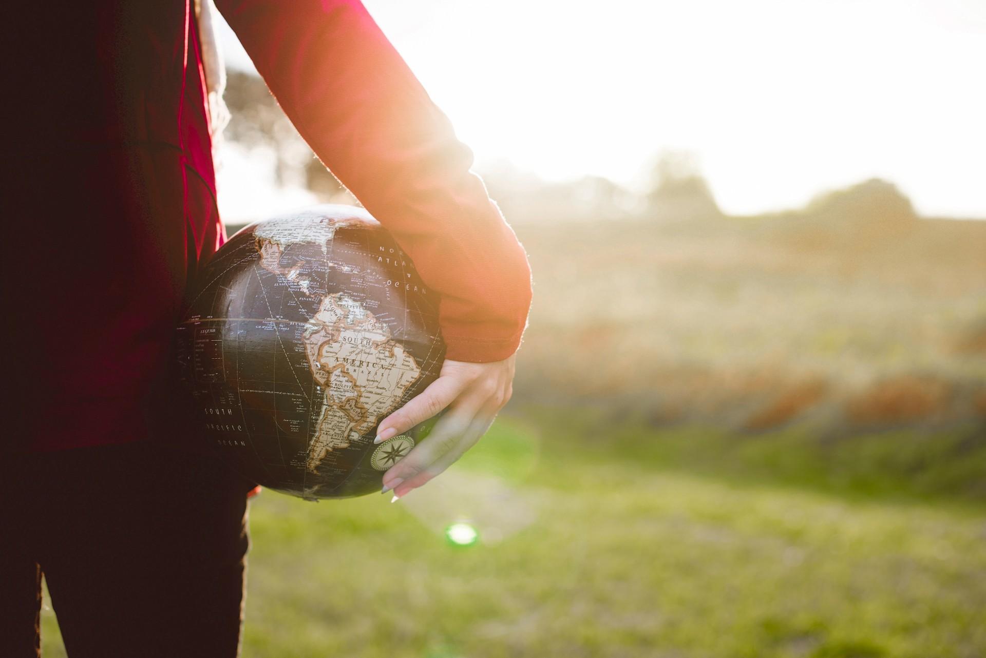 Women holding globe in hands girl earth outdoors green grass travel goals