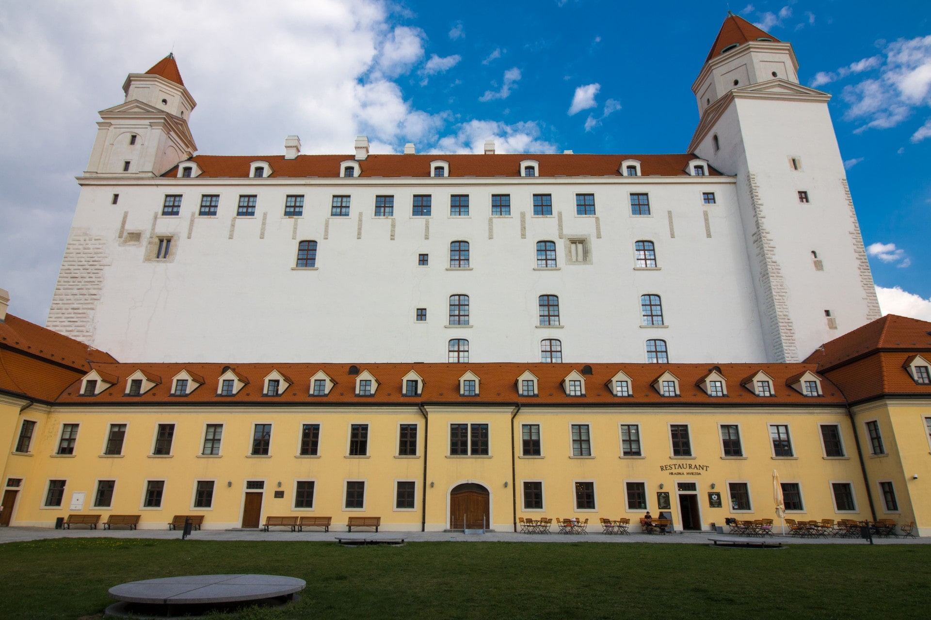 colourful-european-castle-with-a-yellow-and-white-exterior-and-orange-roofs-with-a-green-lawn-in-front-and-blue-skies-behind-bratislava-castle-one-day-in-bratislava