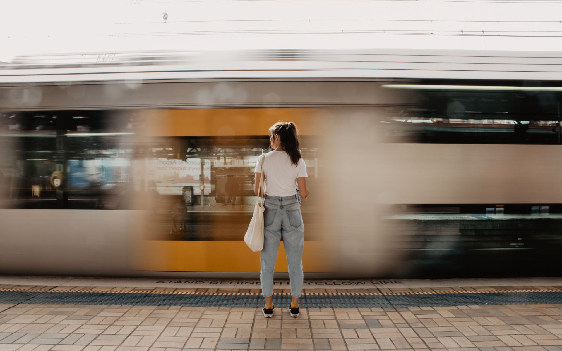 girl-wearing-a-white-t-shirt-and-baggy-light-blue-mom-jeans-standing-at-a-train-station-platform-as-a-train-rushes-past-in-the-background-interrail-budget-interrailing-on-a-budget