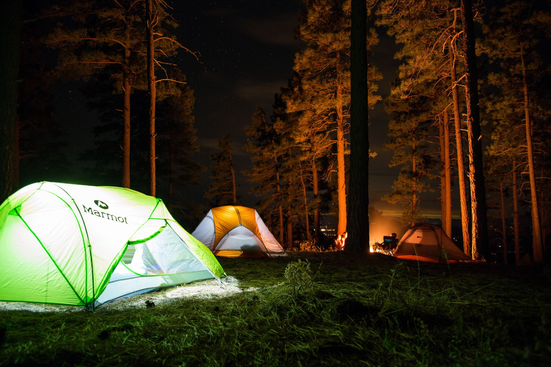 green-and-orange-tents-in-forest-at-night-lit-up-by-bonfire-torches-and-light