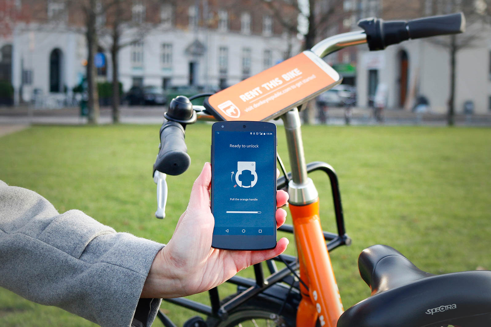 persons-hand-holding-a-phone-with-an-app-open-to-unlock-a-bike-with-an-orange-bike-in-a-park-in-the-background