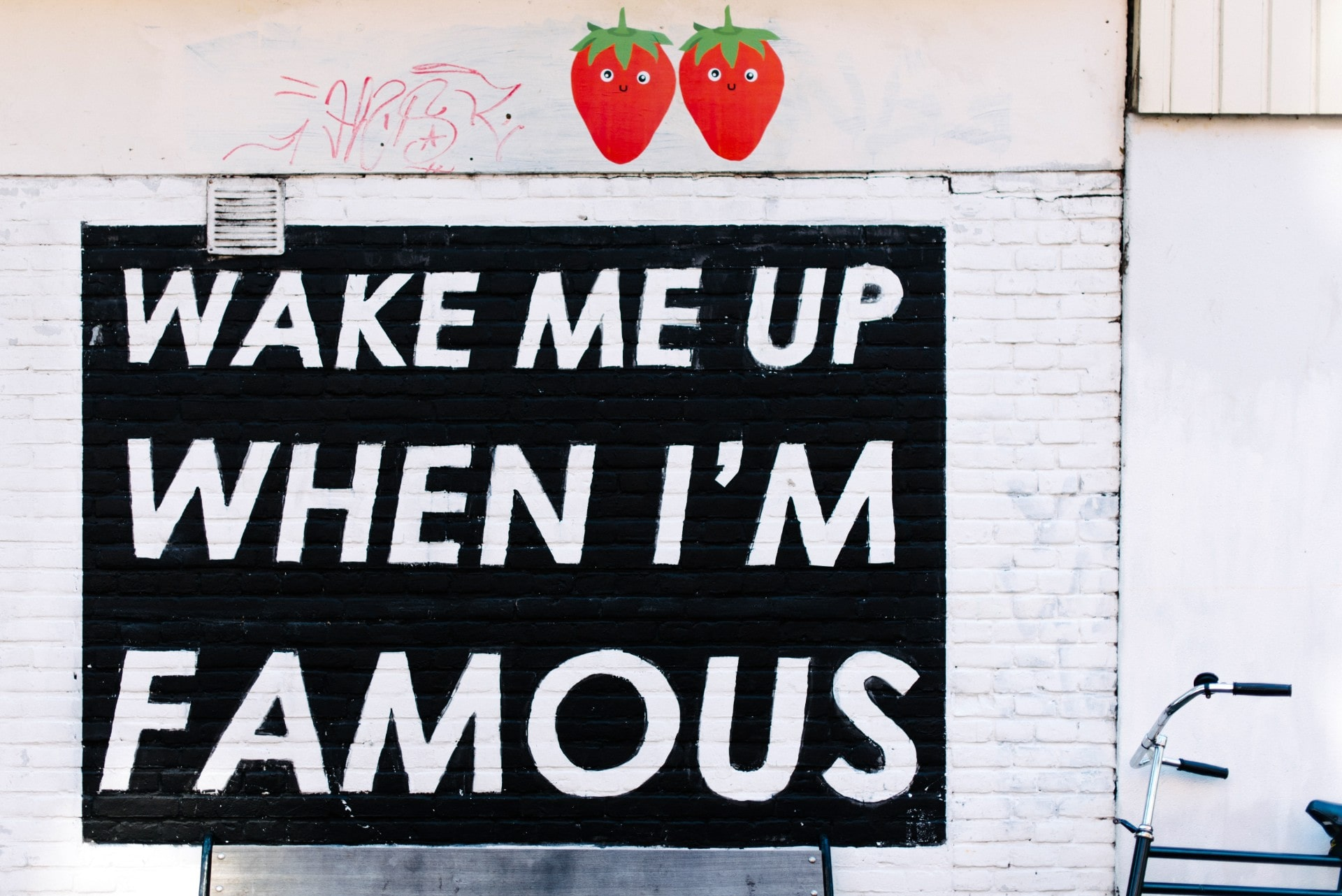 famous-instagrammable-street-art-grafitti-that-says-wake-me-up-when-im-famous-against-white-wall