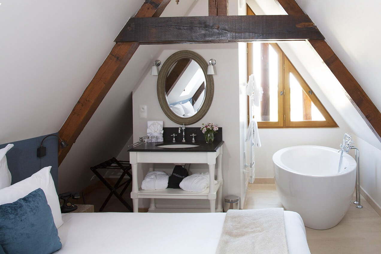 Bedroom hotel room bed mirror vanity sink A framed house freestanding white bath tub window France hotels 15 Romantic Travel Gift Ideas for Valentine's Day