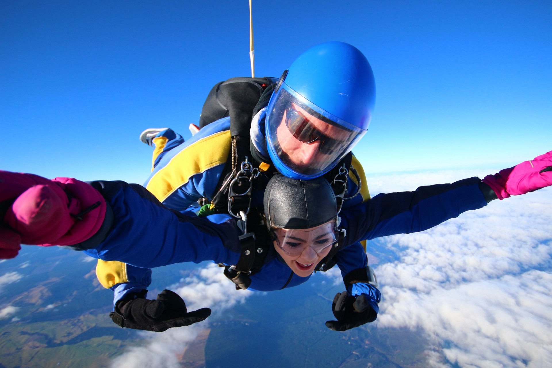 Girl skydiving blue skies clouds pink gloves Skydive Taupo The Best Skydiving in New Zealand