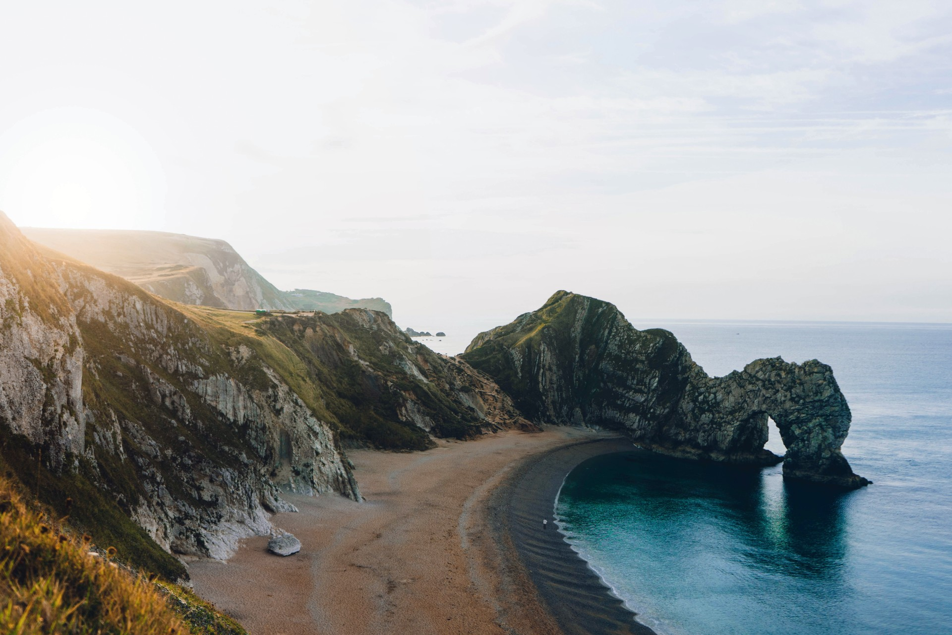 Beach sea cliff sand seaside rock formation Durdle Door Dorset England UK 8 Great Day Trips from Exeter You Can't Miss. Exeter day trips. England, UK. Day trips from Devon. Day trips from Exeter Devon. Day trips from Exeter UK. Day trips from Exeter by train. Day tours from Exeter. Day tours from Exeter UK. Coach day trips from Exeter. Things to do in Exeter. Things to see in Exeter. Things to do in Devon. Exeter travel blog. Exeter travel guide. Bath. Bristol. Cardiff. Plymouth. English Riviera. Jurassic Coast. Dartmoor National Park. Cornwall. Sunset. Golden hour. Click through to read more...