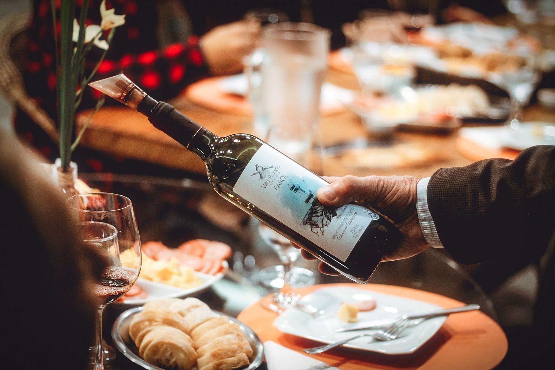Bottle of wine in fancy restaurant. Food, dinner, glasses, flowers. 15 Romantic Travel Gift Ideas for Valentine's Day