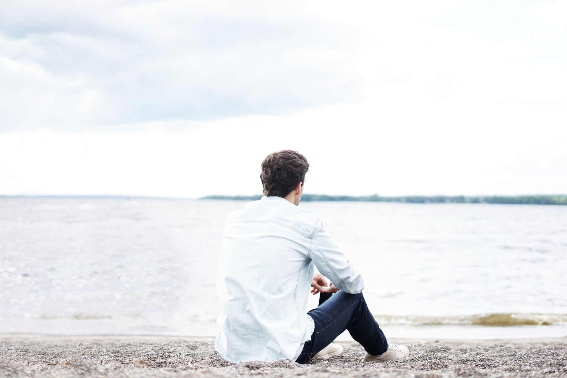 Man in white shirt and jeans sat on a pebble beach looking out to sea contemplating life mellow sad thinking introvert independent Long distance relationship tips. Long distance relationship advice. Click through to read more...