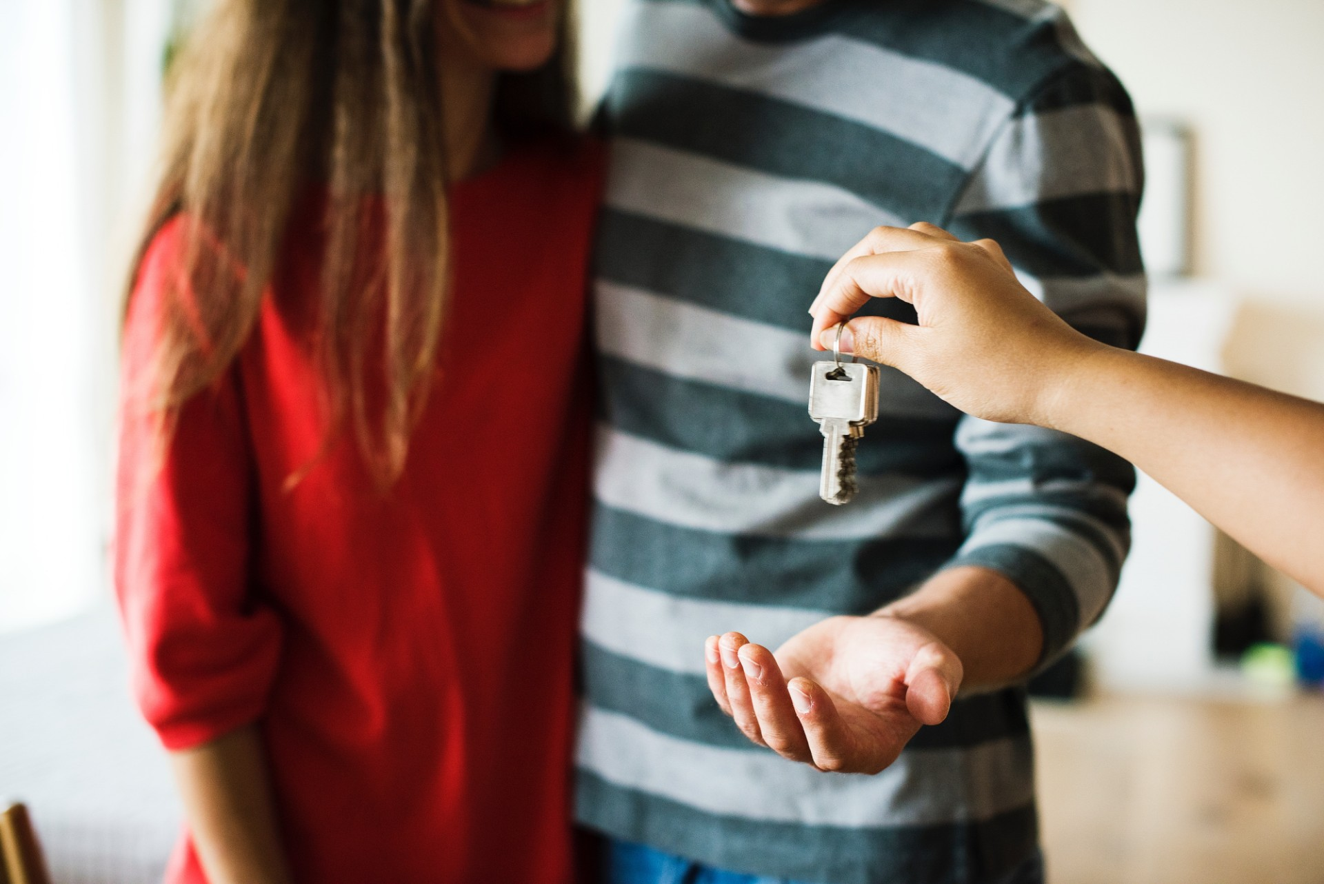 Arm handing a couple keys to their new home. A man and a woman moving in together. Striped jumper and red jumper. 10 Best Tips to Make a Long Distance Relationship Work. Long distance relationship tips. Long distance relationship advice. Click through to read more...