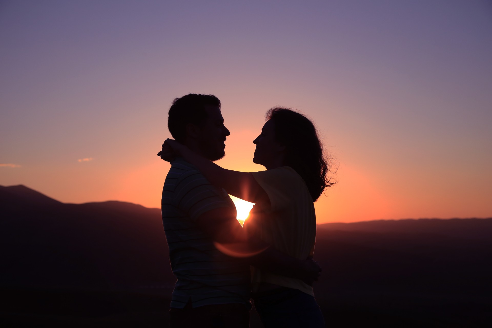 Couple hugging silhouette sunset purple and orange skies love man and woman on mountain in field Long distance relationship tips. Long distance relationship advice. Click through to read more...