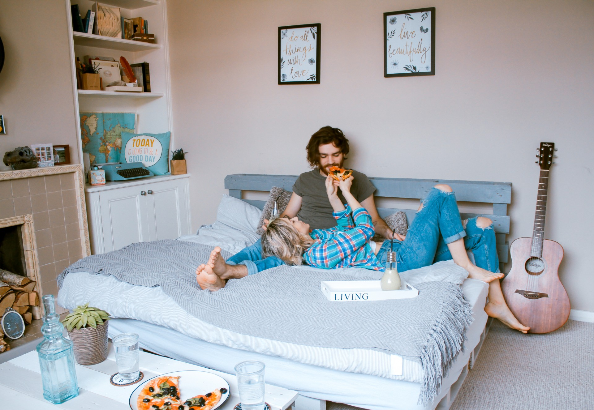 Man and woman a couple lying in bed and snacking on food bedroom with queen size bed guitar pizza plant fireplace and prints on wall Long distance relationship tips. Long distance relationship advice. Click through to read more...