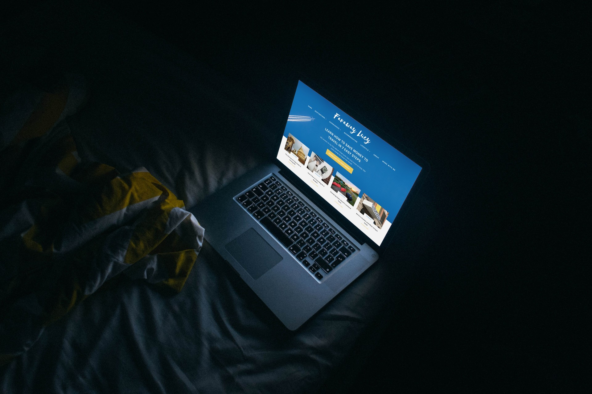 Faraway Lucy travel blog Lucy Ronan laptop with website on screen in dark room at night on a bed How to Get Into Marketing with an English Degree
