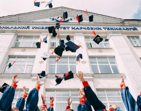 Graduation graduating university graduates throwing their hats in the air in front of a white building How to Get Into Marketing with an English Degree