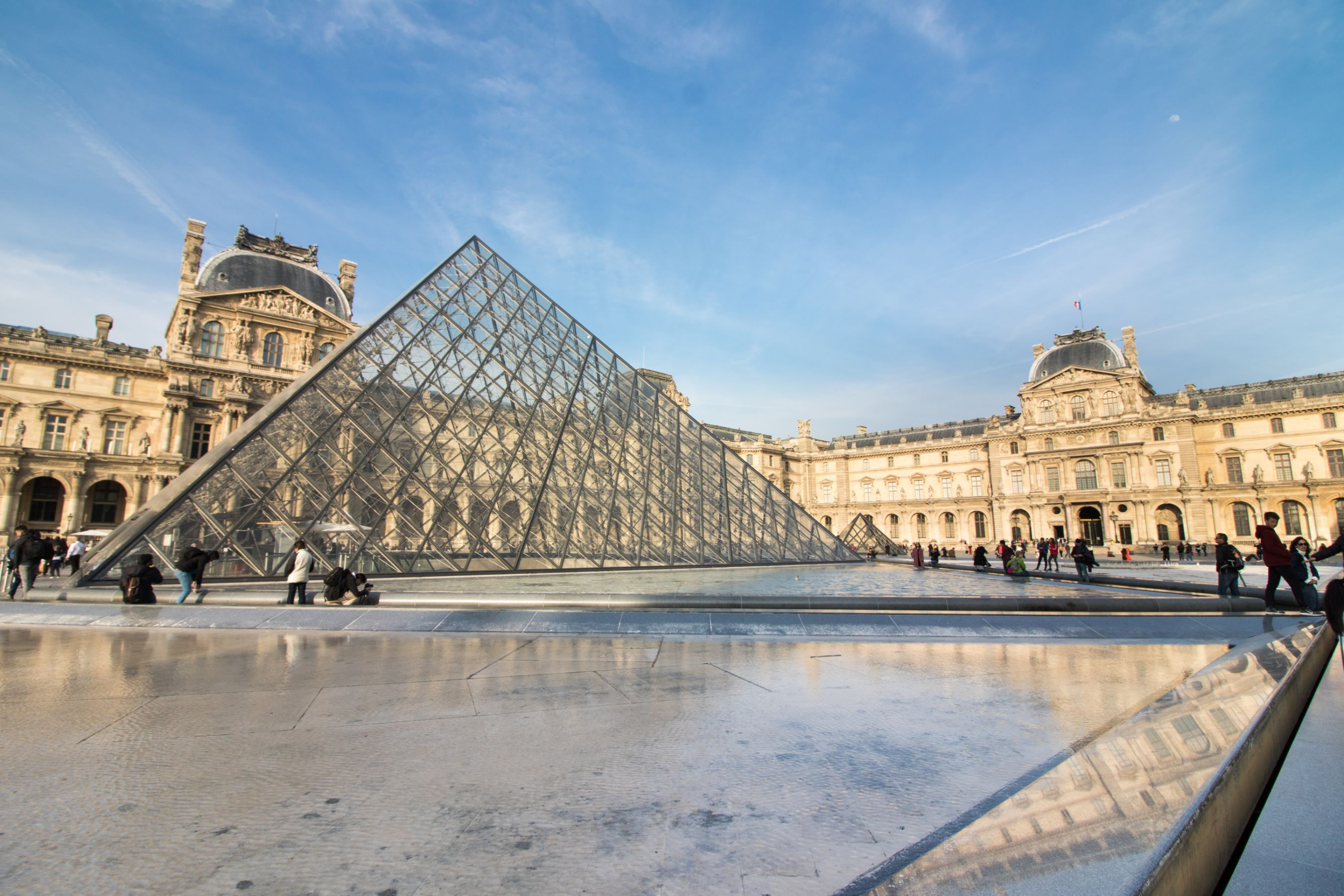 The Louvre Paris. Tourist hotspot in Paris. Clear pyramid triangle in Paris with fountains in front and beautiful, historic buildings in the back and blue skies. Paris travel blog. Paris travel guide. Things to do in Paris. What to do in Paris. Places to See in Paris. Things to see in Paris. What to see in Paris. Click through to read more...