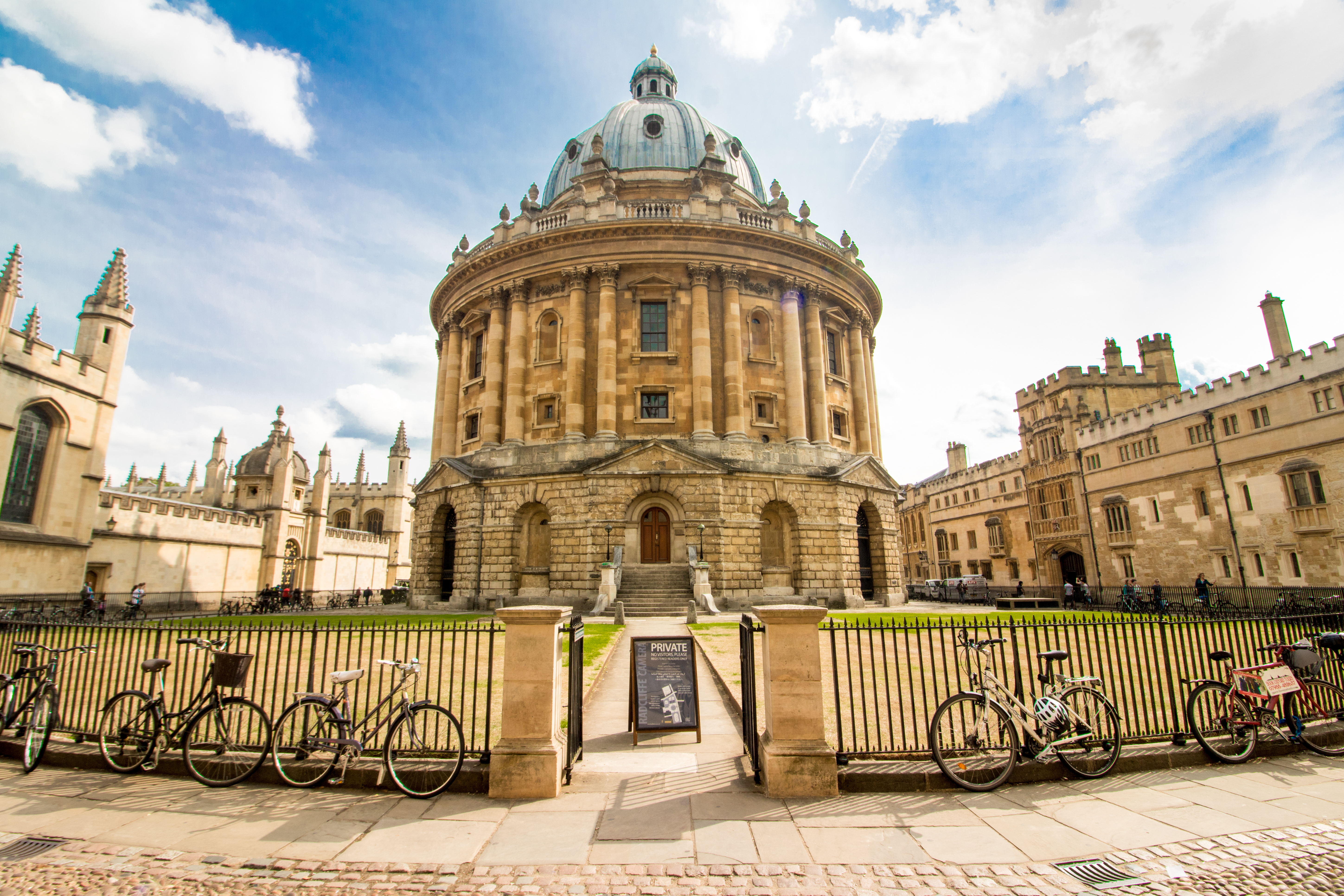 Radcliffe Camera. Bicycles lined up in front of old historic building with a green lawn in front. Castle. Blue skies. How to Spend One Day in Oxford: Best Things to Do. Oxford England. Oxford UK. Oxford University. 24 hours in Oxford. Oxford in One Day. Things to do in Oxford. Places to see in Oxford. Places to Visit in Oxford. What to see in Oxford. Things to see in Oxford. What to do in Oxford. Oxford attractions. Oxford top attractions. Oxford travel blog. Oxford travel guide. Oxford Castle. Turl Street. Oxford bookshops. Bridge of Sighs. Bodleian Library. Radcliffe Camera. University Church of St Mary. Oxford punting. Click through to read more...