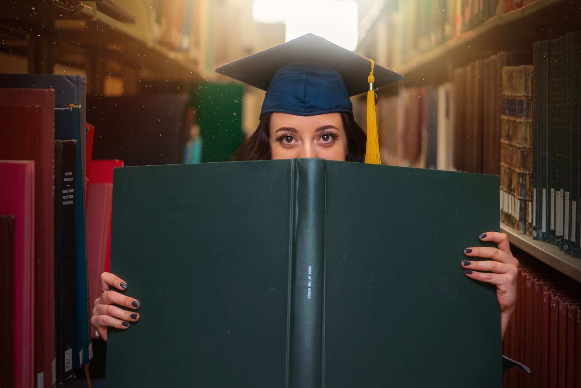 Female graduate wearing a mortar board holding a book in a library. 9 Things I Wish I Knew When I Started University