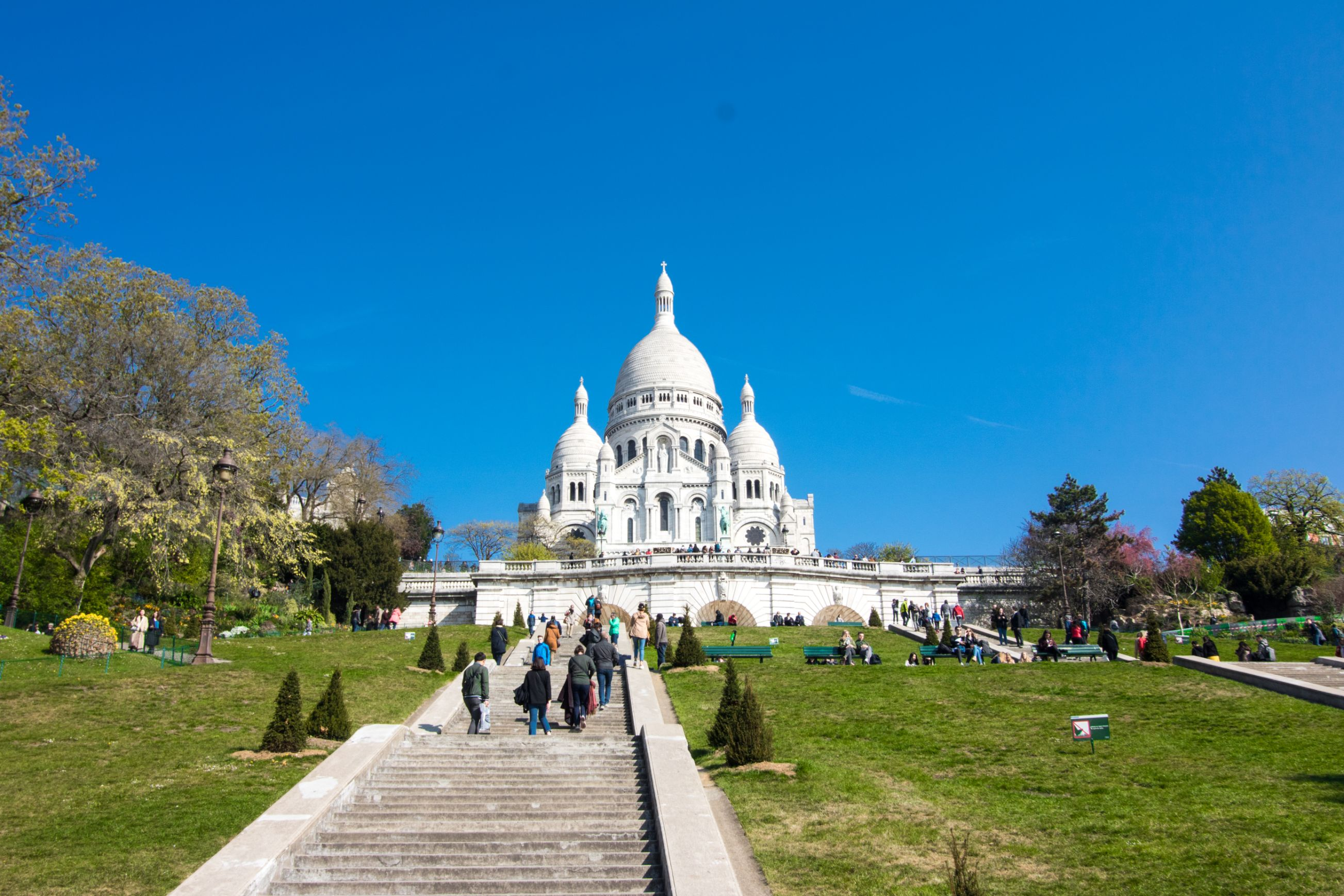 Sacre-Couer Basilica in Montmartre in Paris. Roman Catholic Church sat on top of steep hill. People walking up a path on a hill towards church on a sunny summer day with blue skies. The Best Way to Easily See Paris in Two Days [Itinerary]. Two days in Paris. Weekend in Paris. Paris in a weekend. Paris weekend travel guide. Weekend Paris travel guide. Paris weekend trip. Paris weekend packing. Weekend Paris trip. Paris two day itinerary. Paris travel tips. Paris travel itinerary. Paris travel blog. Paris travel guide. Things to do in Paris. What to do in Paris. Places to See in Paris. Things to see in Paris. What to see in Paris. Paris France. Paris photography. Click through to read more...