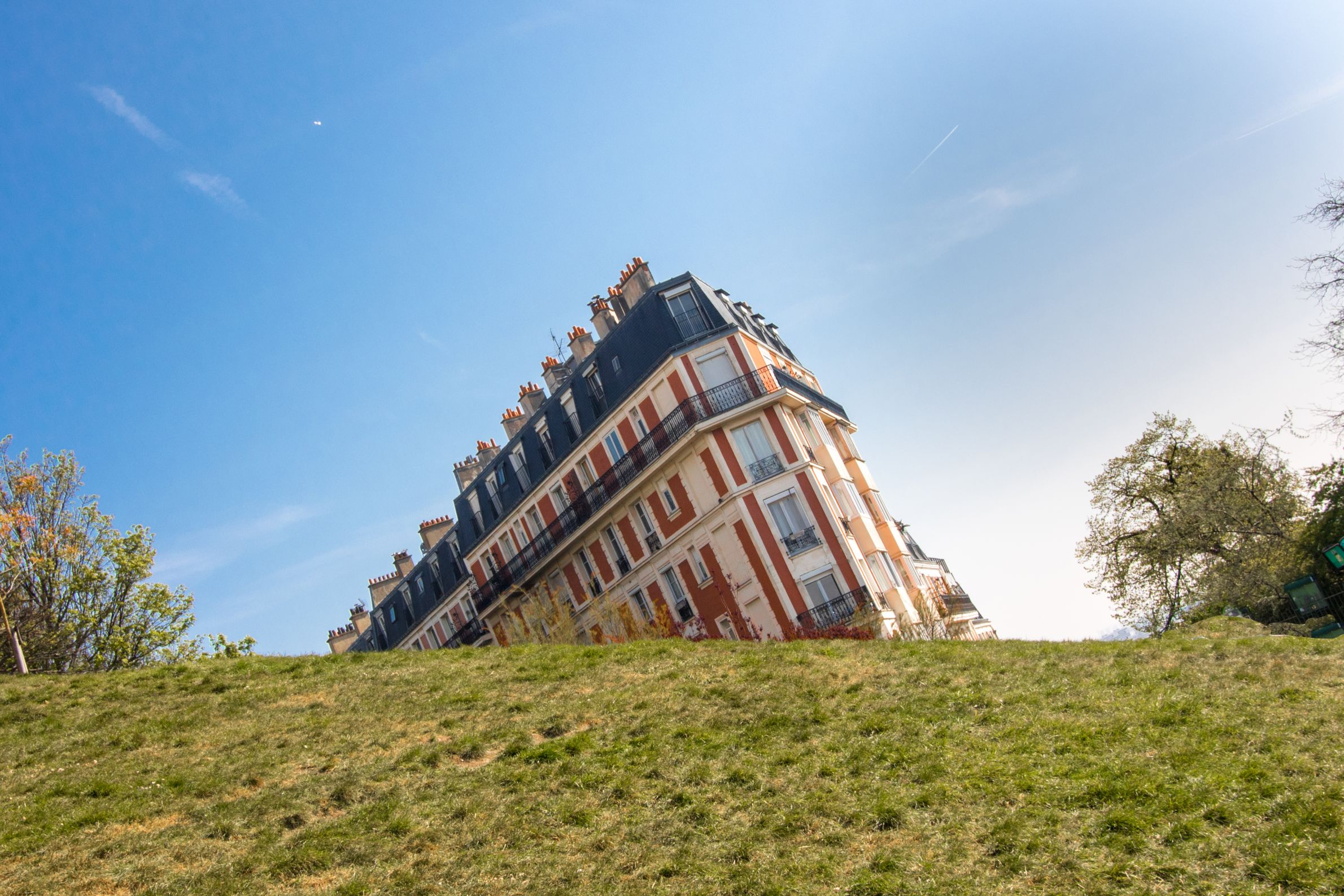 Sinking House of Montmartre in Paris by Sacre-Coeur Basilica. An optical illusion of a building sinking into a grassy bank.