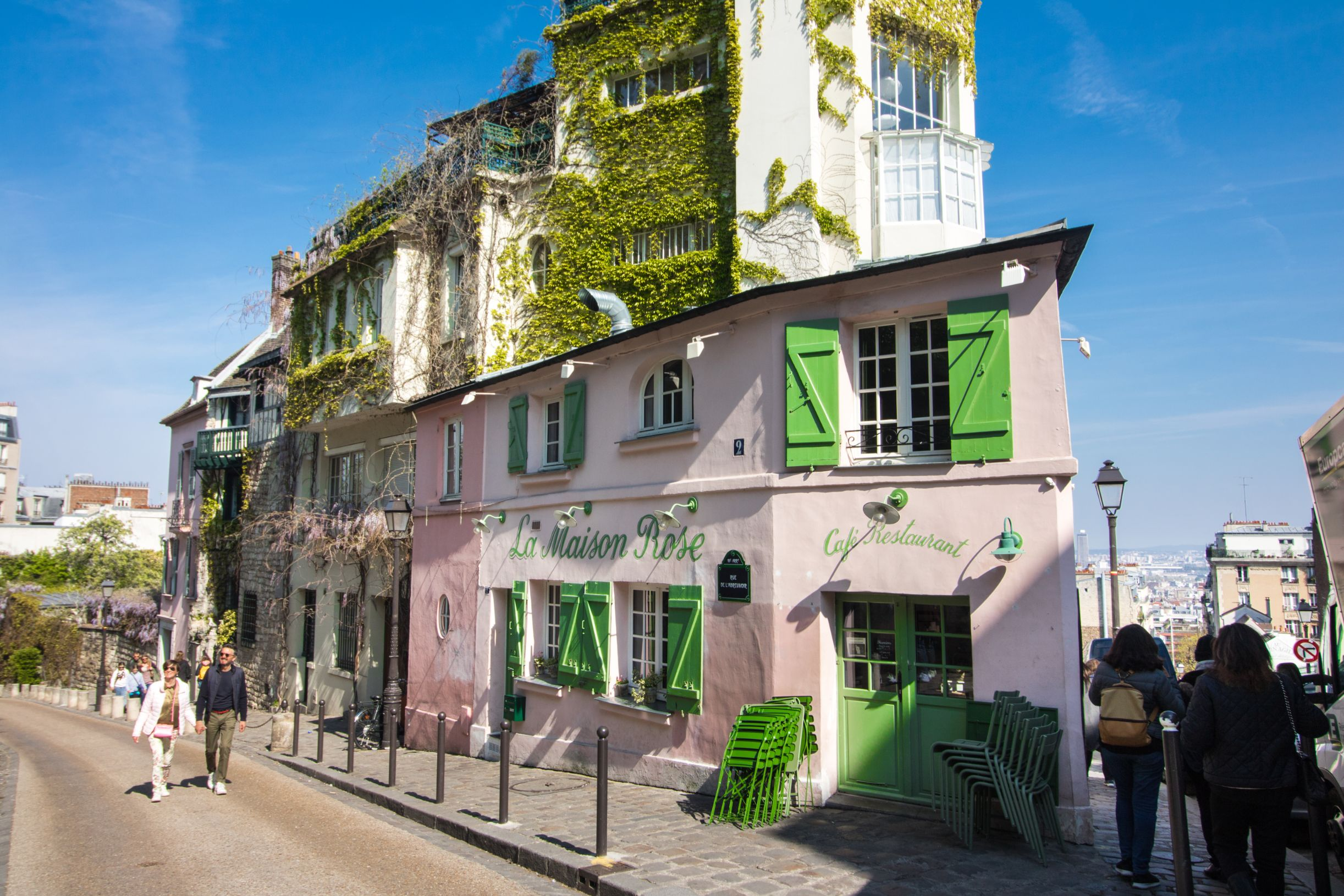 La Maison Rose in Montmartre Paris. Iconic pink Instagrammable cafe in Paris with bright green windows and doors and ivy climbing up the walls. Blue skies.
