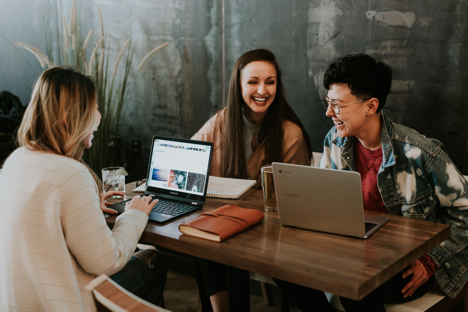 Work colleagues and friends laughing at a table whilst working on their laptops. 9 Things I Wish I Knew When I Started University