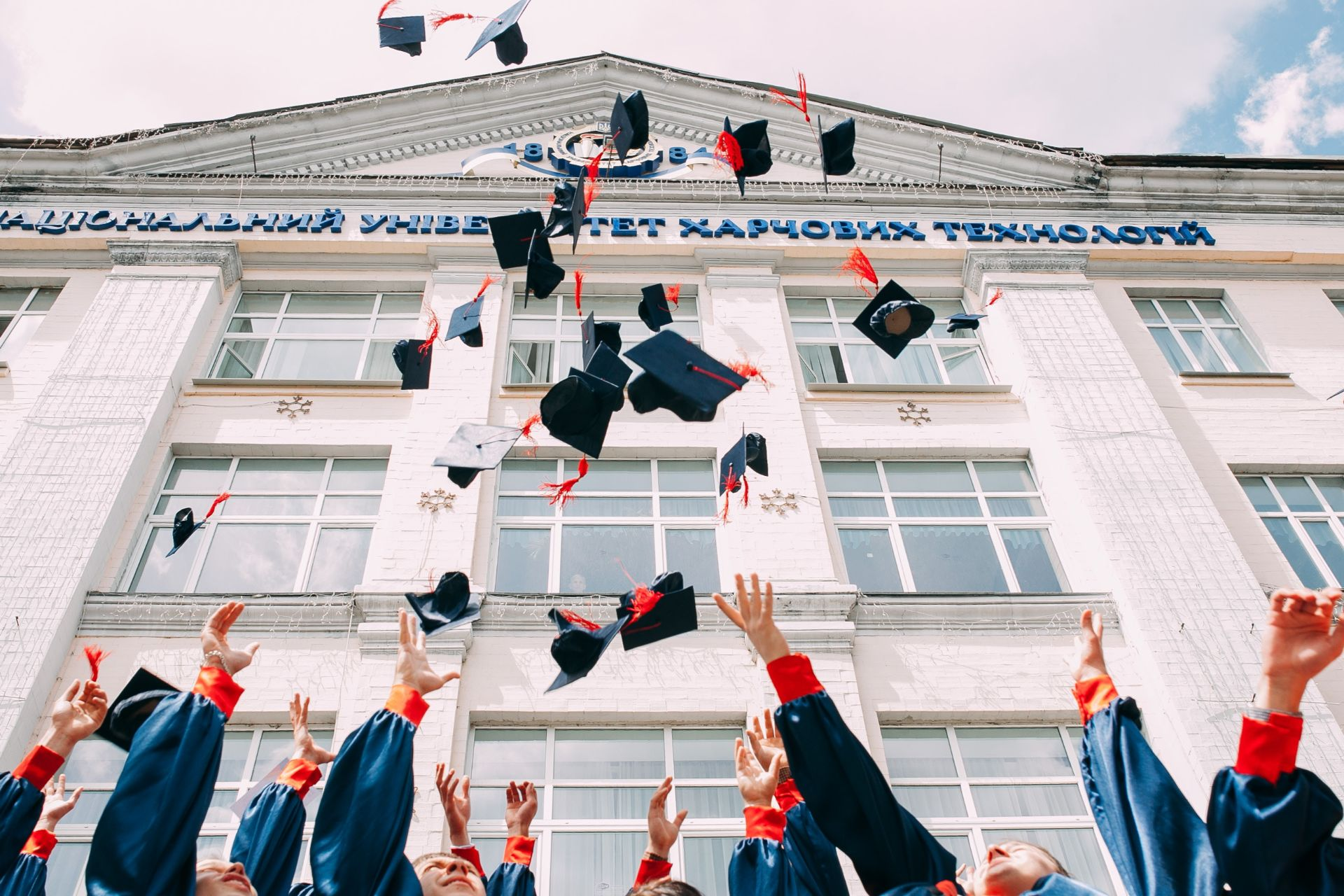 Graduates from university celebrating and throwing their mortar boards up in the air in front of a historic university building. 9 Things I Wish I Knew When I Started University