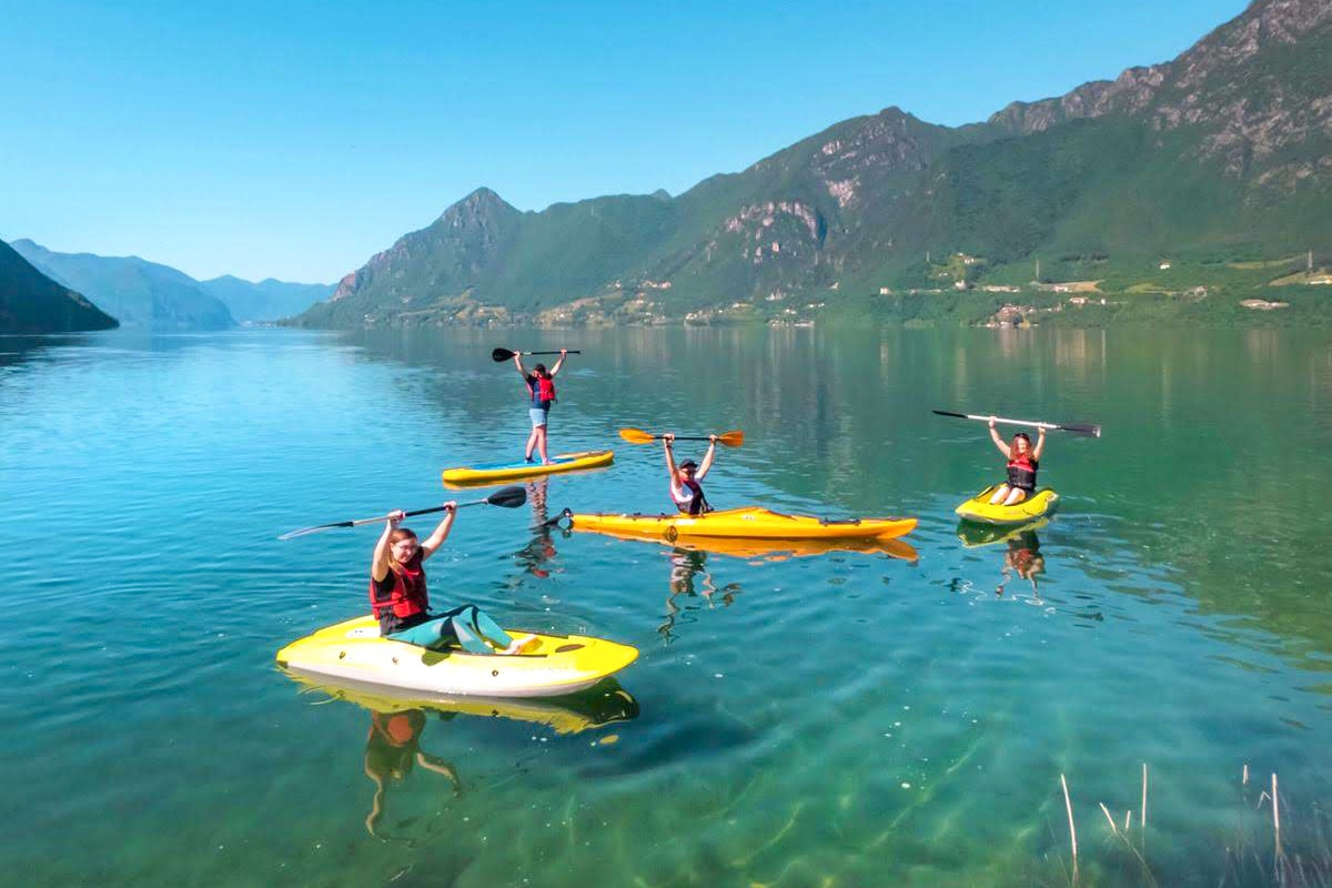 four-girls-kayaking-and-stand-up-paddleboarding-on-crystal-clear-lake-surrounded-by-mountains-lake-idro-valle-del-chiese-trentino-italy