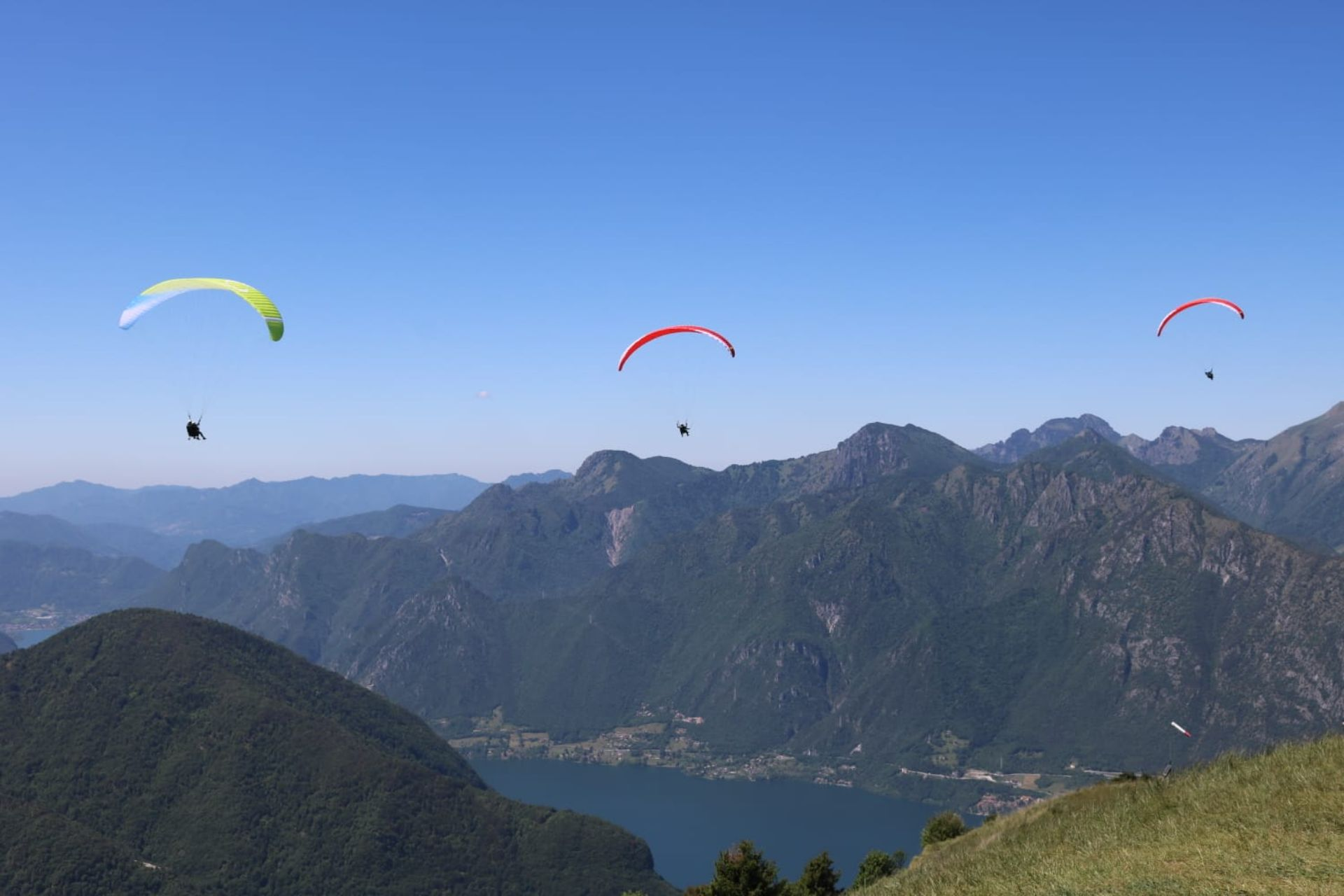 paragliders-flying-from-italian-mountain-towards-lake-paragliding-valle-del-chiese-trentino-italy