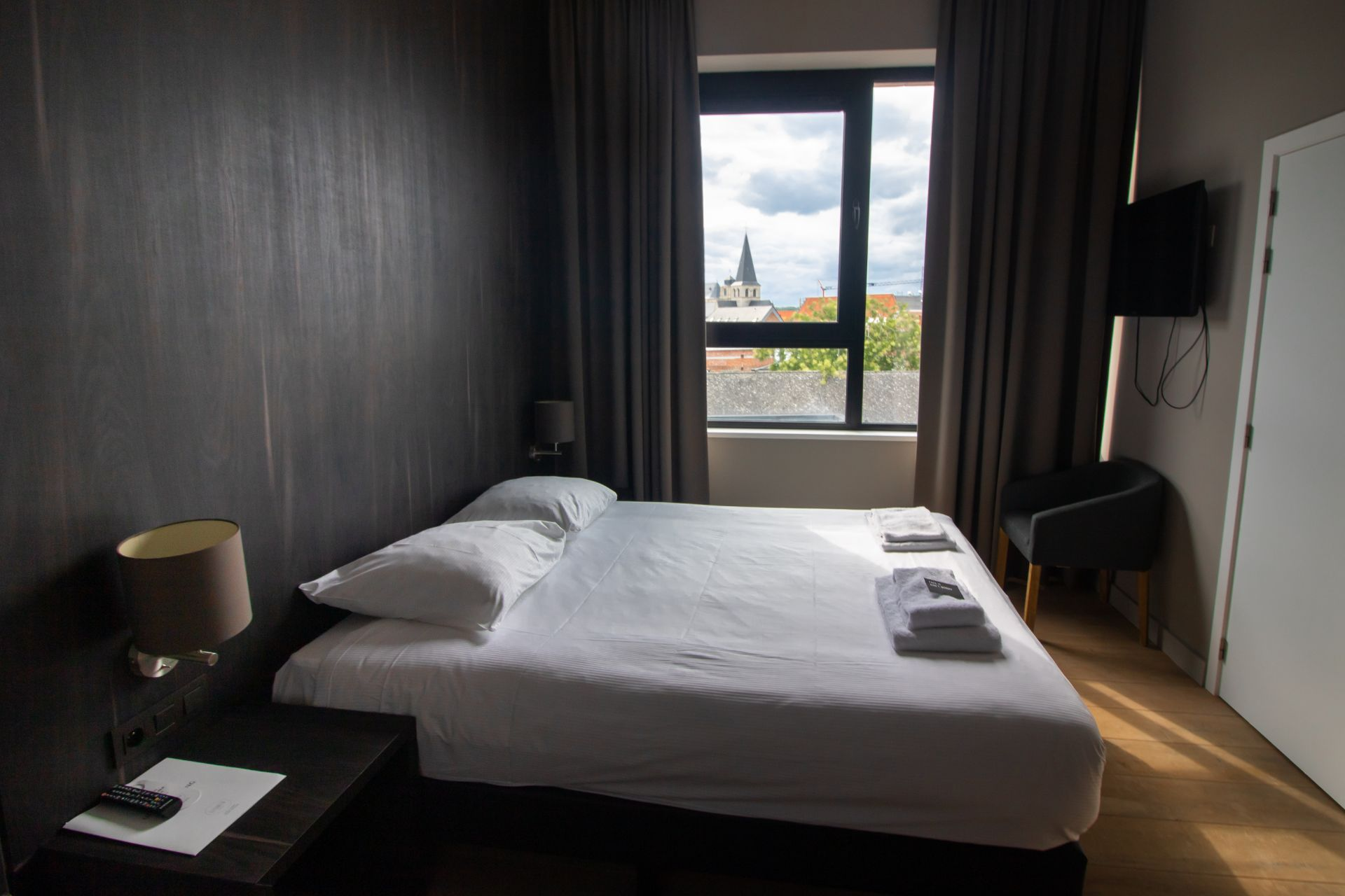 hotel-room-with-double-bed-bedside-table-chair-and-tv-with-a-view-overlooking-a-european-city-hotel-elisabeth-mechelen-belgium