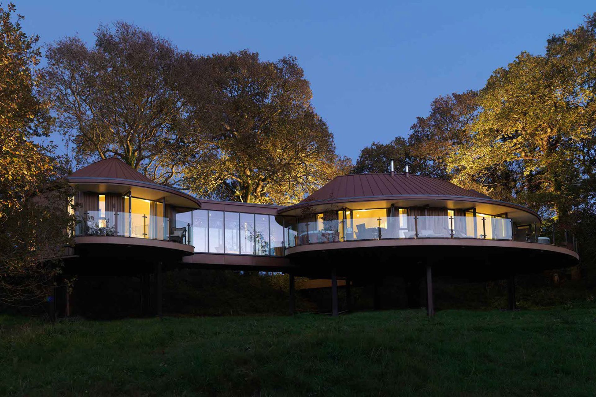 luxurious-treehouse-hotel-on-stilts-lit-up-at-night-chewton-glen-new-forest-hampshire