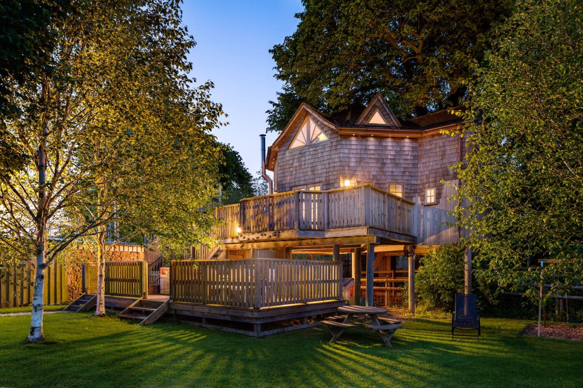 luxurious-treehouse-hotel-with-patio-in-garden-lit-up-at-night-lavender-hill-holidays-taunton-somerset-treehouse-holidays-uk-with-hot-tub