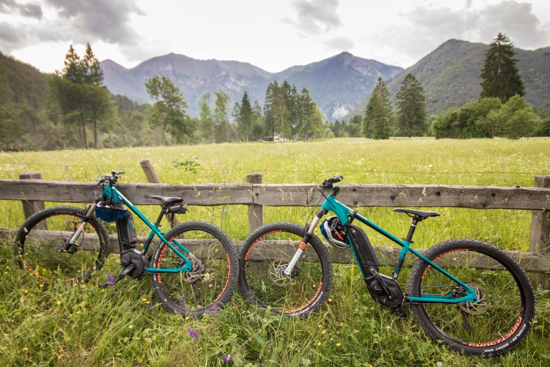 mountain-bike-ebikes-leaning-against-a-fence-in-a-field-with-mountains-in-the-background-valle-di-ledro-lago-di-ledro