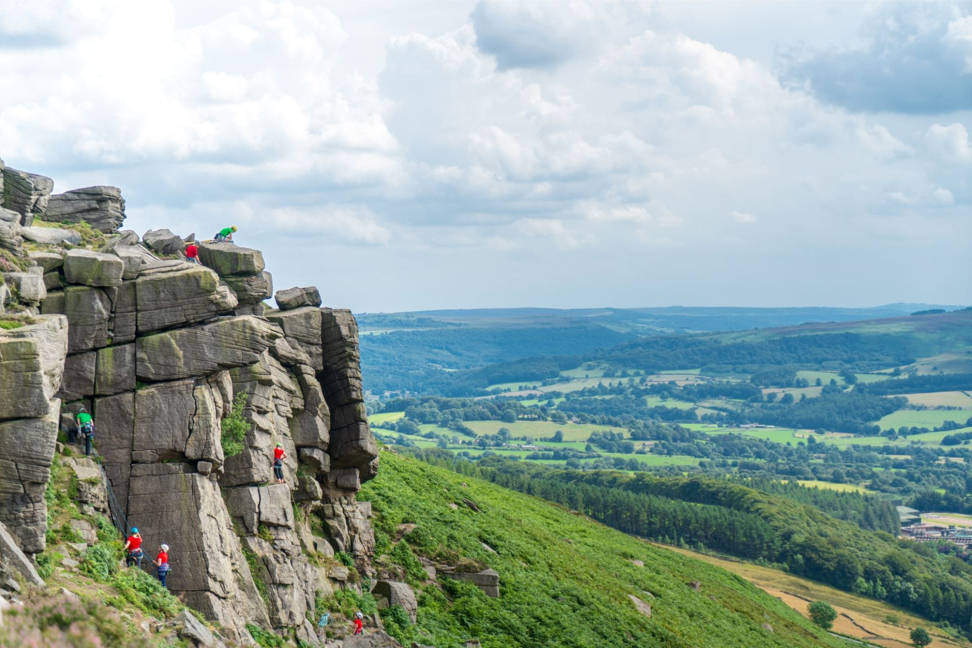 people-rock-climbing-up-a-rock-edge-with-rolling-green-hills-in-background-at-bamford-edge-in-the-peak-district