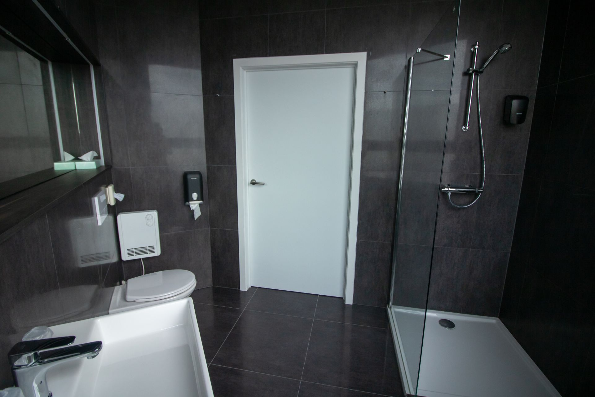 sleek-modern-black-hotel-bathroom-with-shower-toilet-mirror-and-sink-hotel-elisabeth-mechelen-belgium