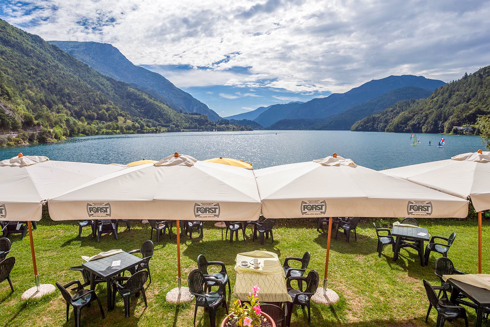 tables-in-garden-of-restaurant-overlooking-a-beautiful-lake-and-mountains-in-the-summer-hotel-lido-valle-di-ledro-lago-di-ledro-trentino-italy