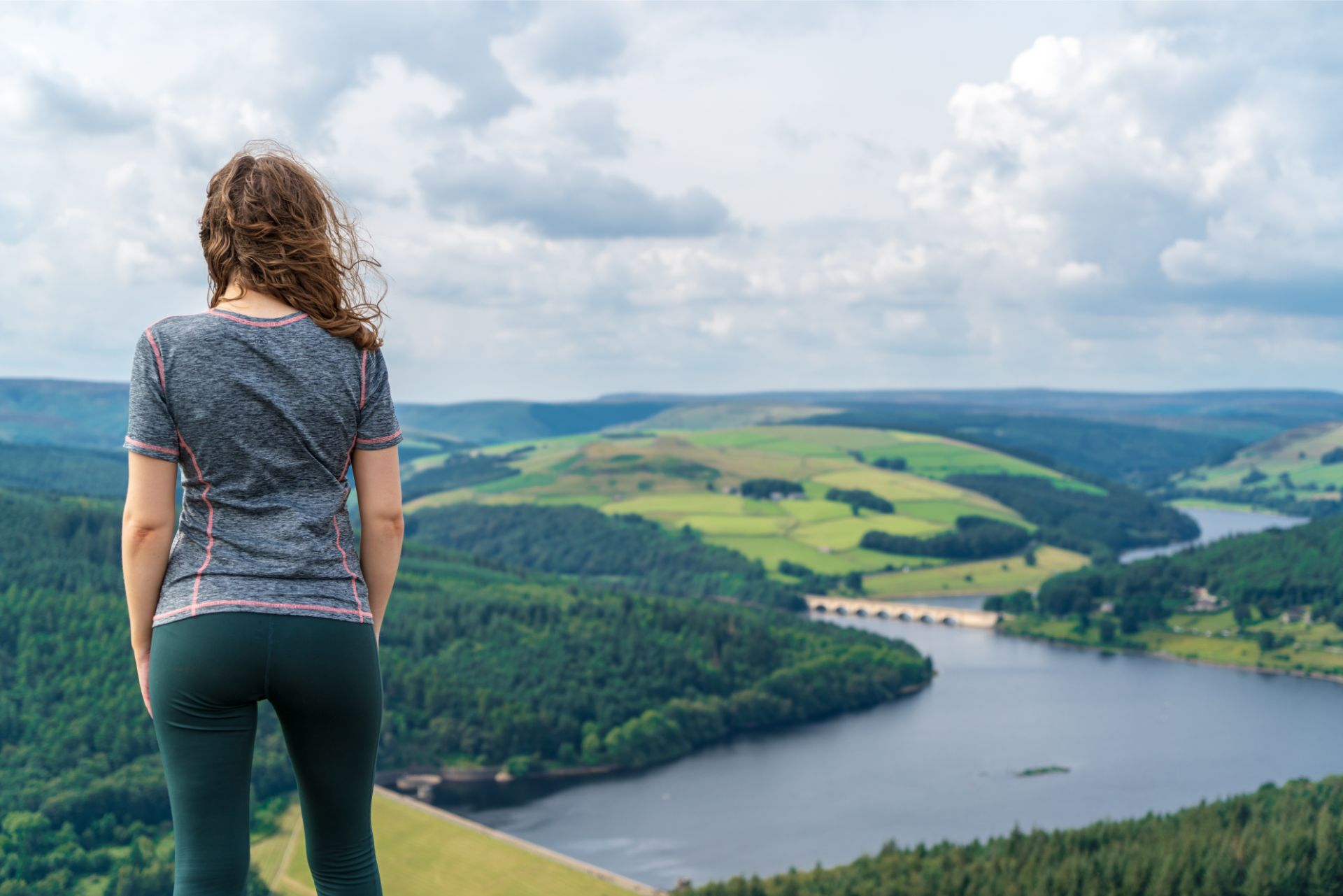 woman-in-sportsgear-standing-on-hill-admiring-a-view-of-a-reservoir-bridge-and-hills-at-bamford-edge-in-the-peak-district