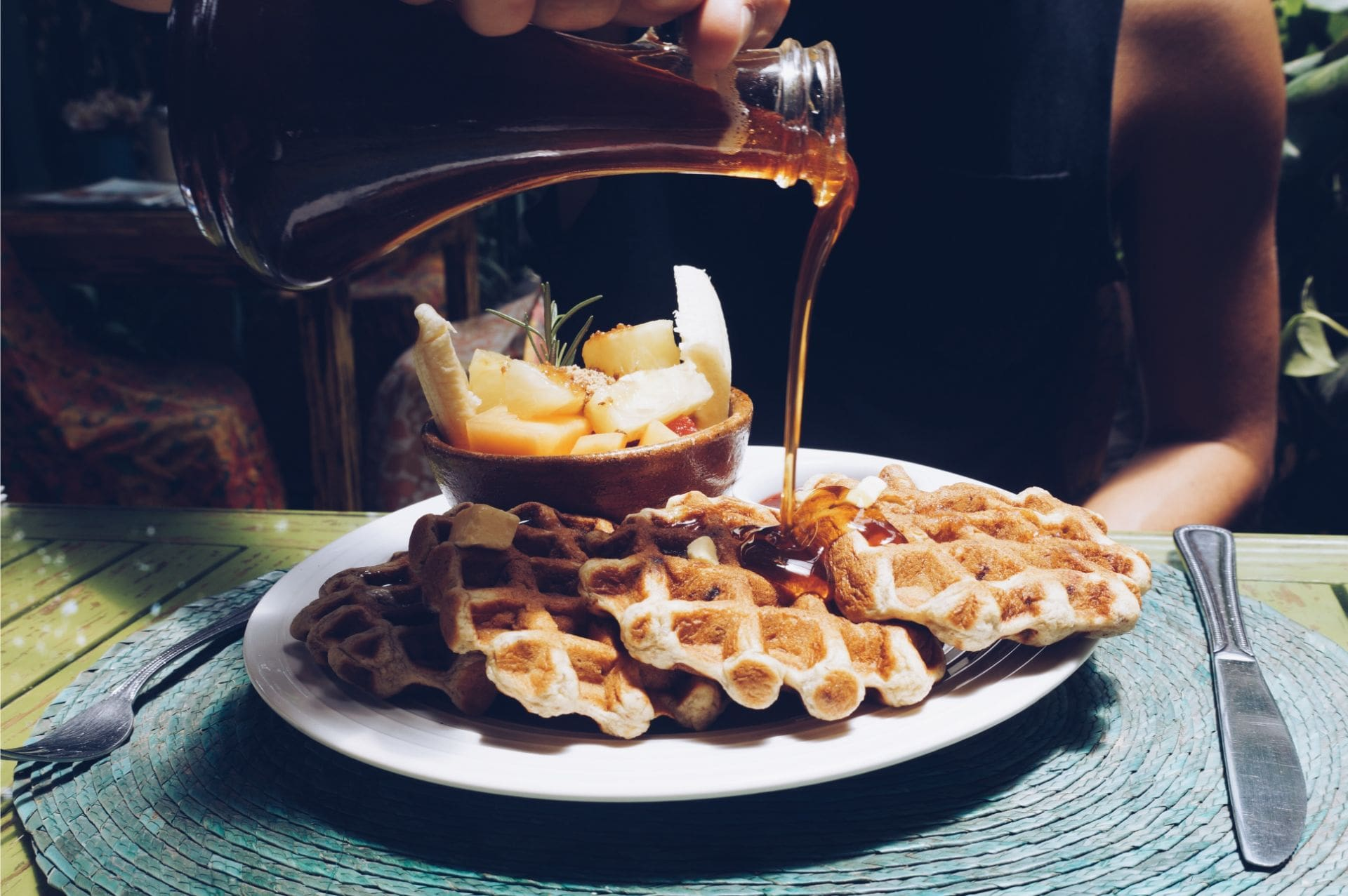 woman-pouring-maple-syrup-over-belgian-waffles-at-restaurant