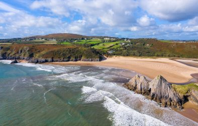 beautiful-sand-beach-with-rolling-green-fields-in-background-three-cliffs-bay-weekend-in-the-gower-swansea-bay-wales