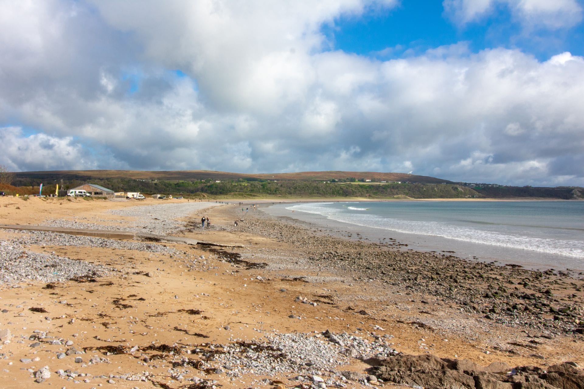 sand-and-stone-beach-against-blue-skies-the-gower-swansea-bay-wales-uk