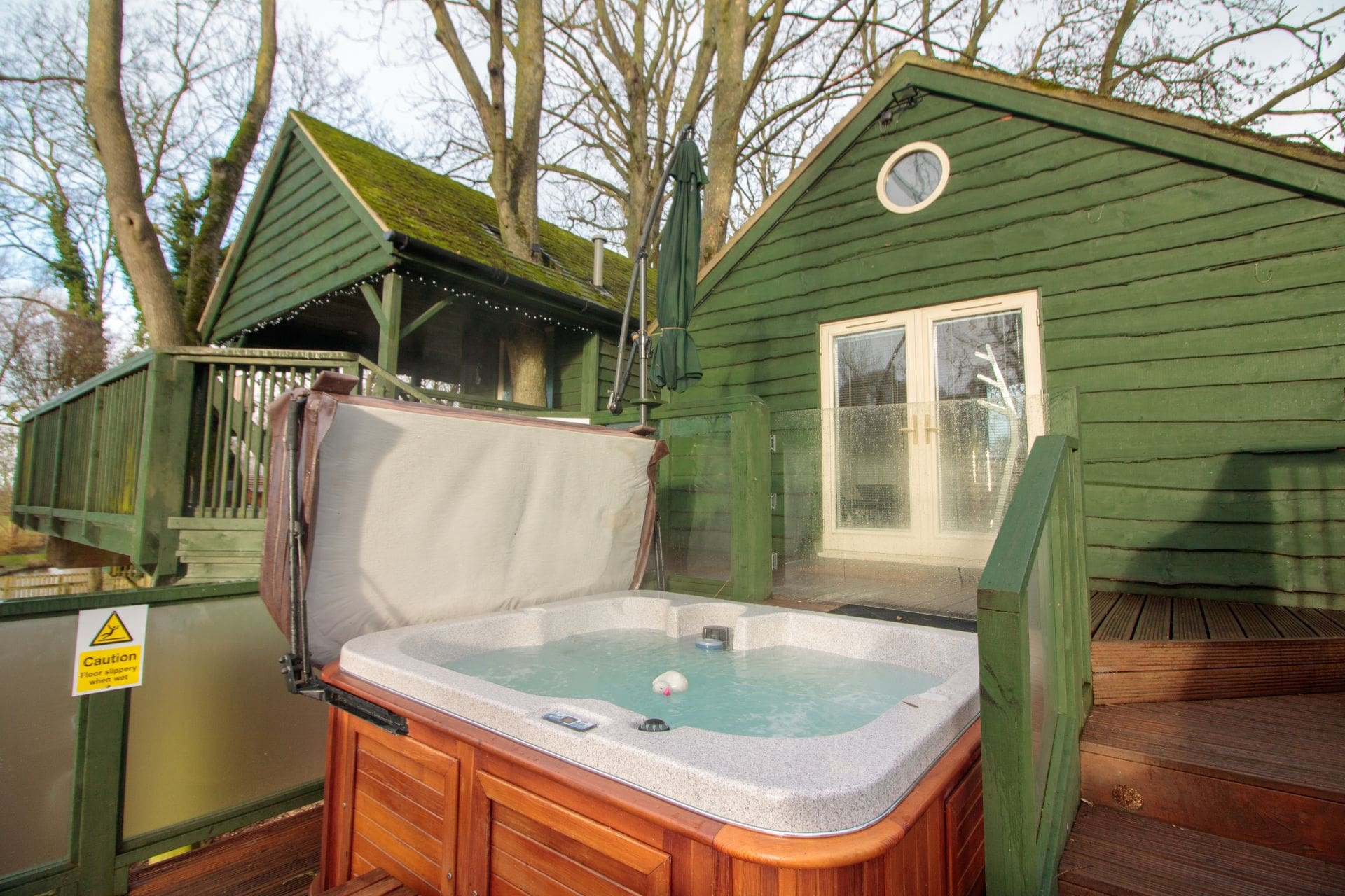 bubbling-outdoor-hot-tub-jacuzzi-on-decking-in-holiday-accommodation-wills-tree-house-treehouse-breaks-uk