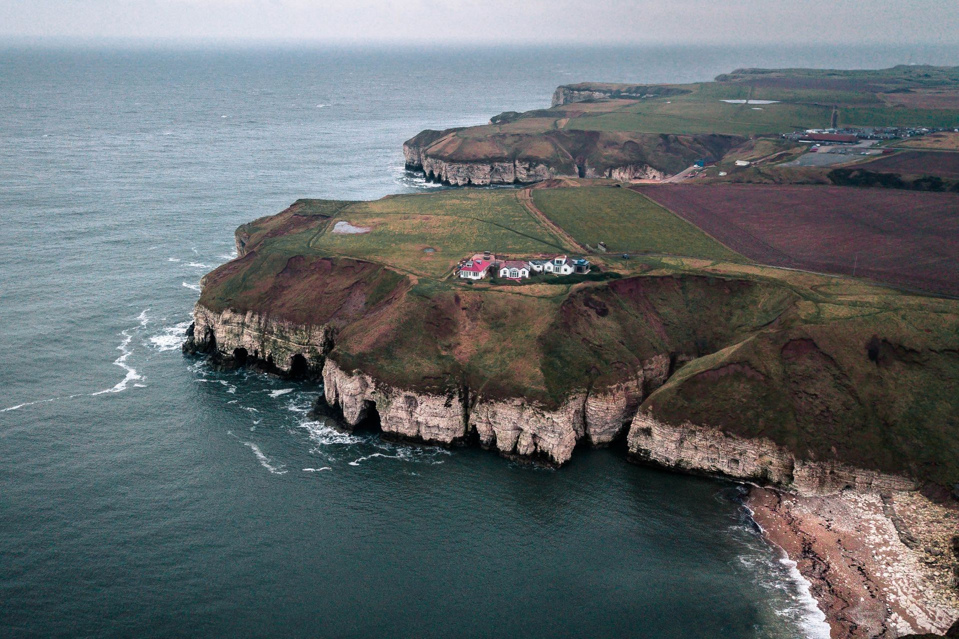 houses-sitting-on-edge-of-cliff-by-the-sea-on-a-dark-moody-autumn-winter-day-in-britain-at-flamborough-head