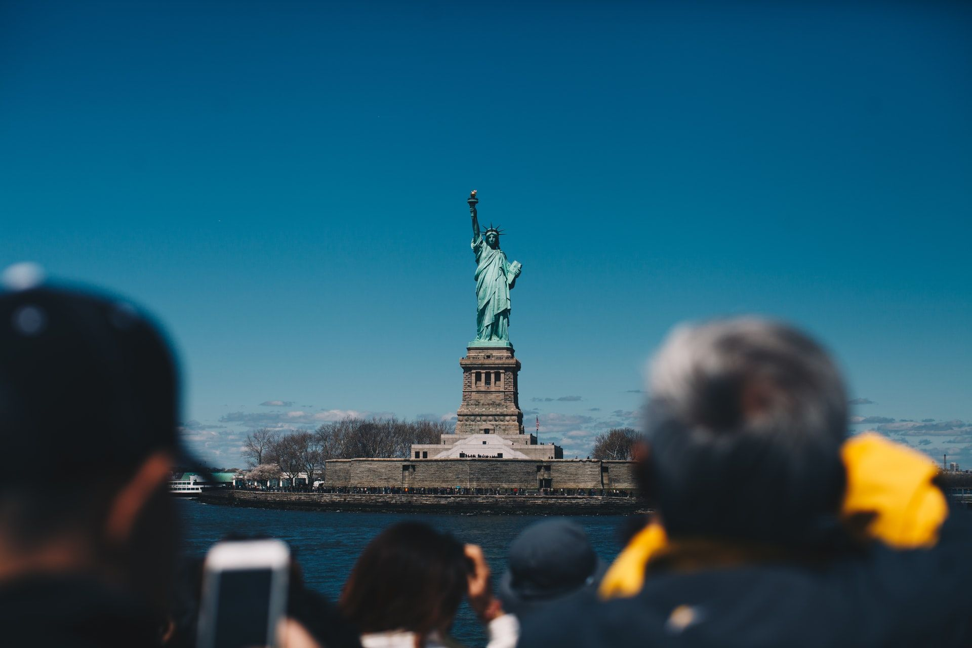 back-of-tourists-heads-taking-photos-on-staten-island-ferry-of-the-statue-of-liberty