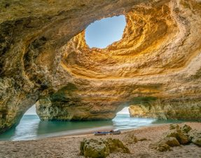 boat-sitting-on-sand-in-sandy-cavern-at-benagil-cave-portugal-in-the-algarve