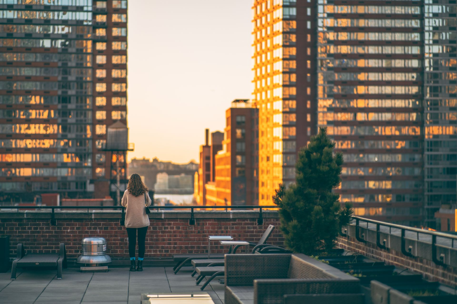 girl-stood-on-apartment-rooftop-in-new-york-city-at-sunset-looking-out-across-the-buildings