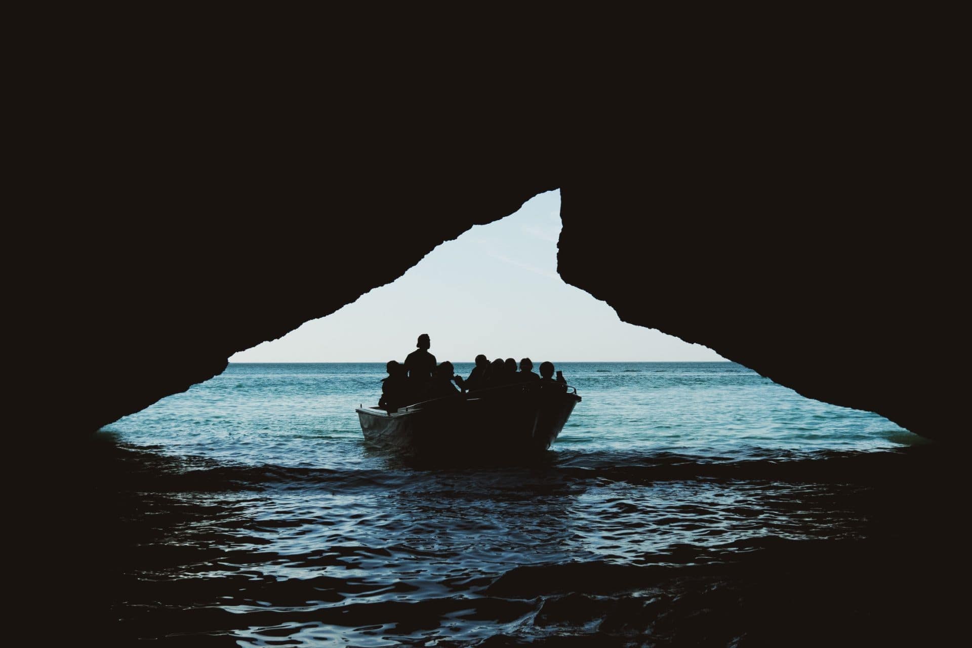 silhouette-of-a-boat-filled-with-people-on-the-water-pulling-into-a-cave