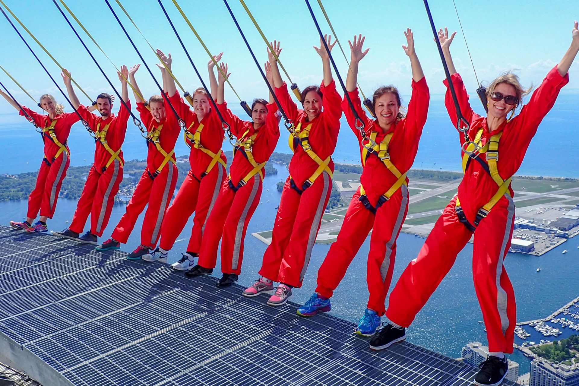 group-of-people-hanging-off-the-edge-of-a-tower-edgewalk-toronto-cn-tower-adrenaline-junkie-bucket-list