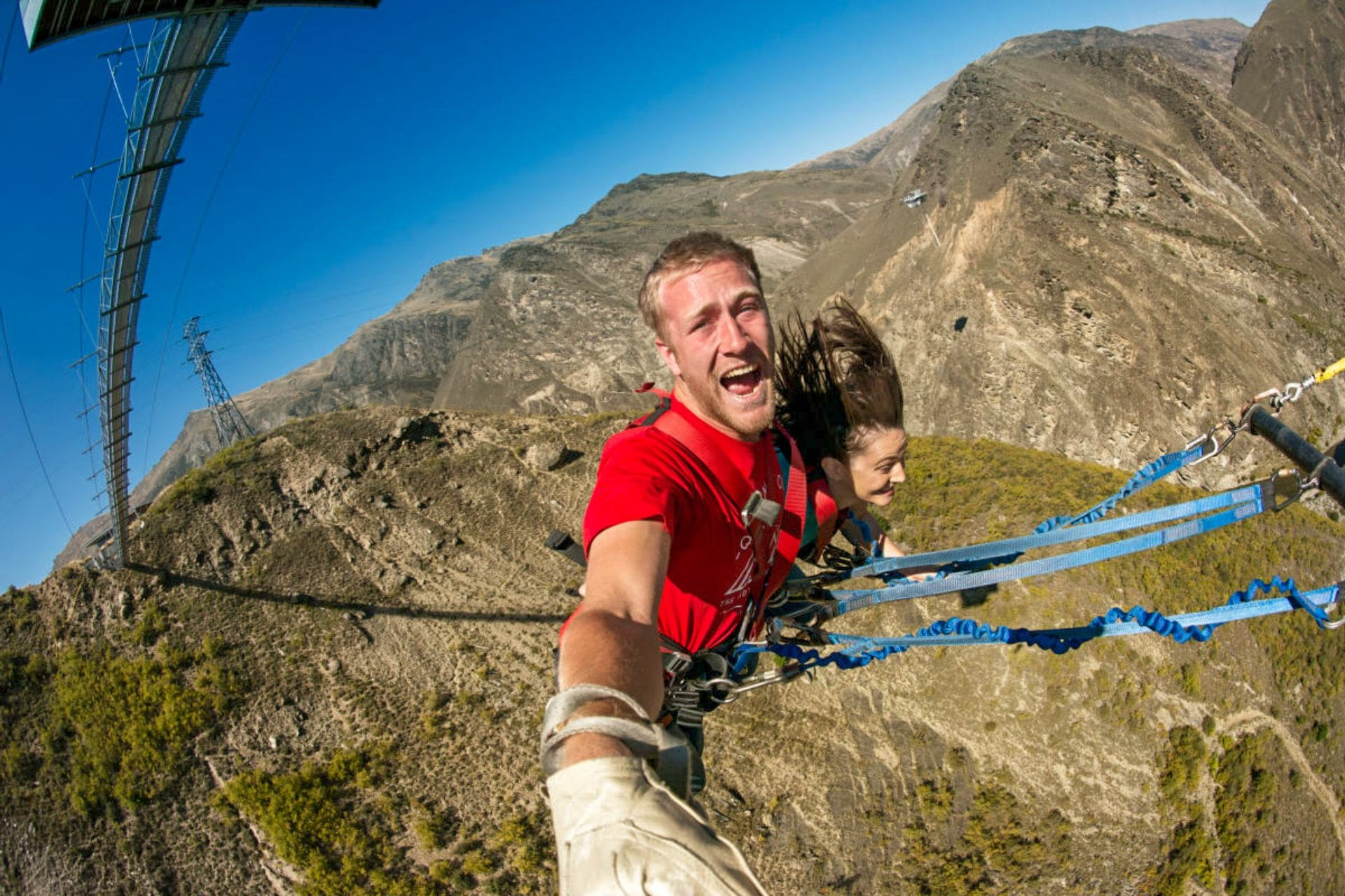 man-and-woman-attached-to-bungy-rope-flying-through-valley-aj-hackett-new-zealand-nevis-swing-adrenaline-junkie-bucket-list