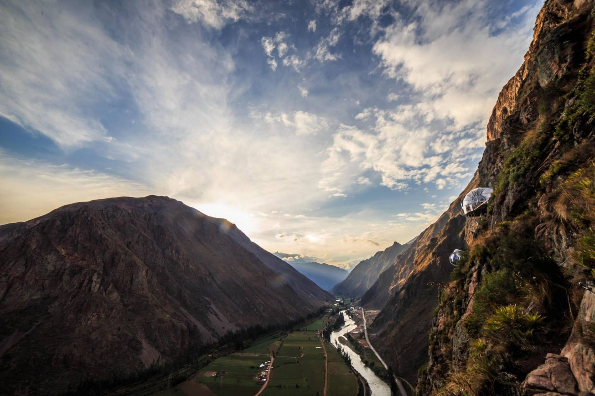pods-hanging-off-cliff-edge-over-valley-with-a-river-running-through-peru-skylodge-adventure-pods-urubamba
