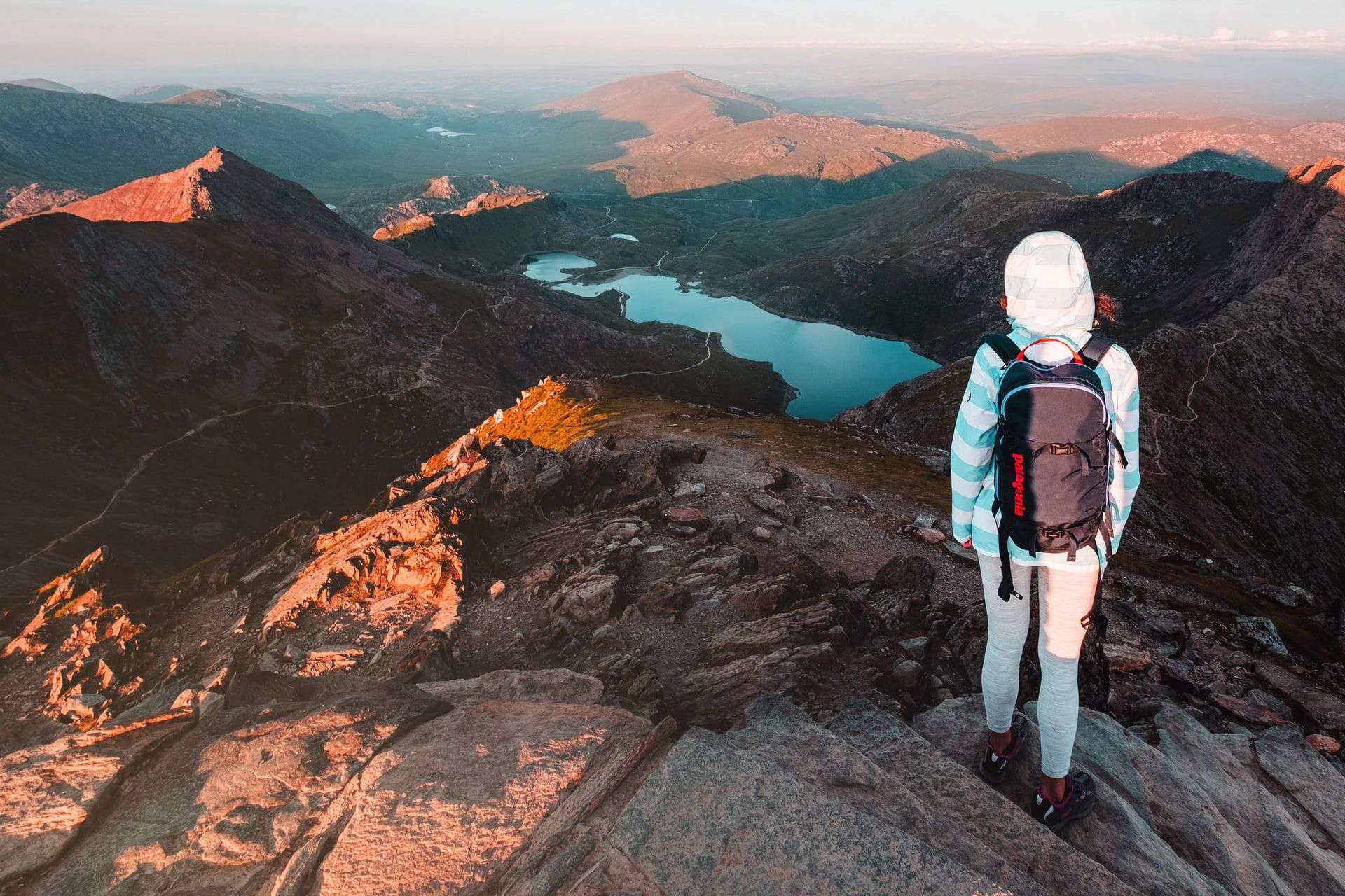 female-hiker-woman-standing-on-top-of-mountain-overlooking-lake-mount-snowdon-snowdonia-outdoor-activities-wales