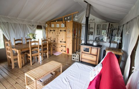 inside-a-safari-tent-glamping-site-with-kitchen-bed-table-and-sofa-harvest-moon-holidays-scotland
